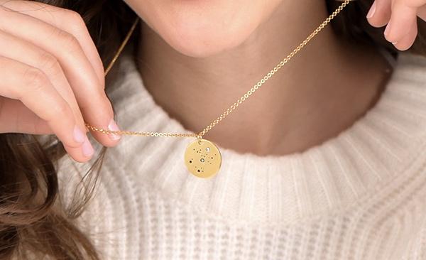 Woman wearing a zodiac necklace with diamond